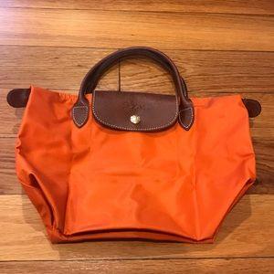 Longchamp small orange bag.